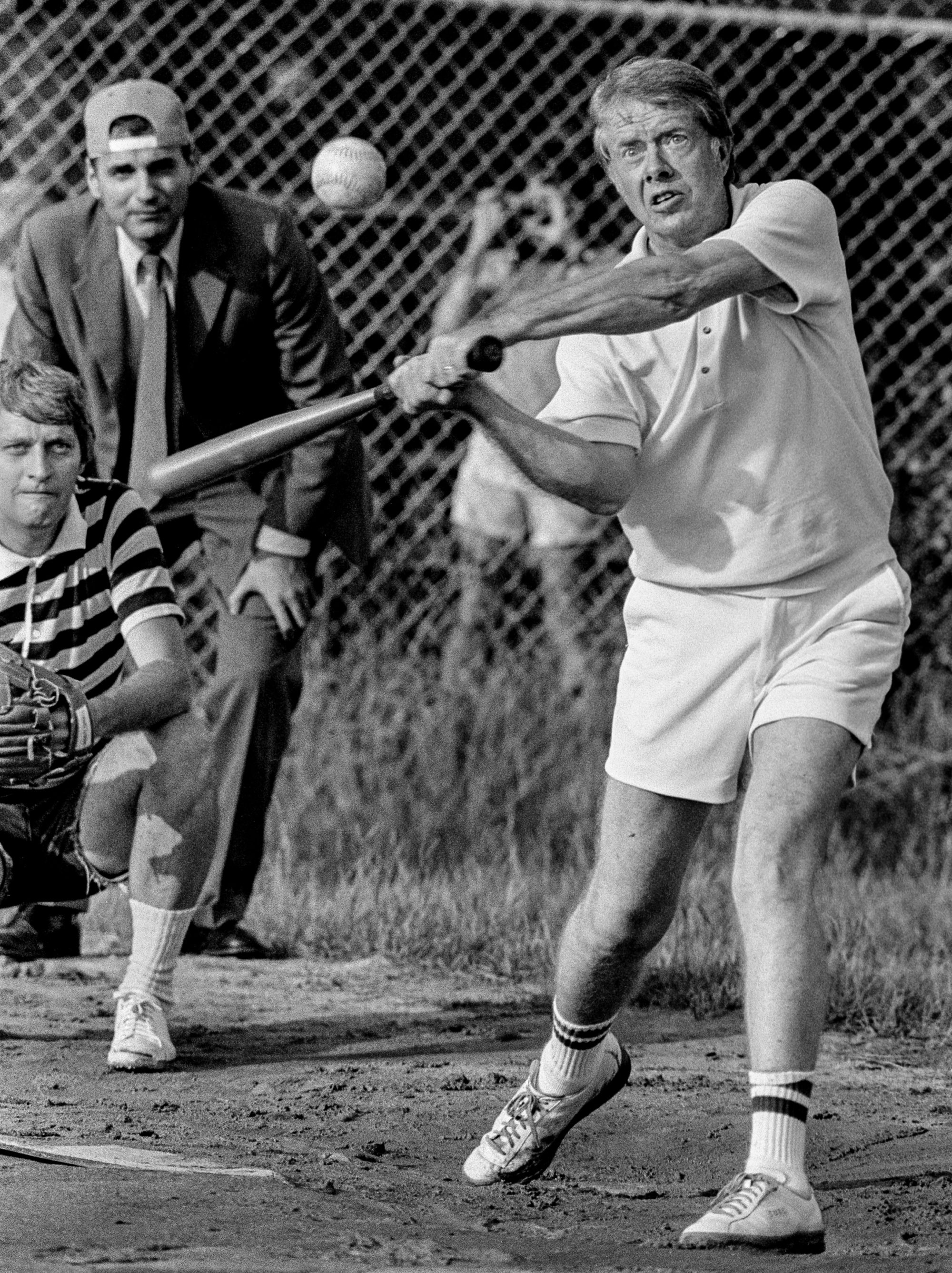 Carter at bat during a softball game at Plains High School. The umpire is consumer advocate and future five-time presidential candidate Ralph Nader the catcher - James Wooten of the New York Times.